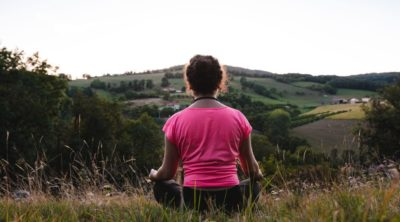woman meditating in field as part of dinacharya