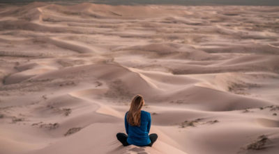 woman meditating in dunes