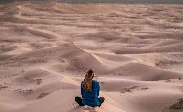 woman meditating in dunes