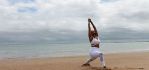 woman practice yoga for digestion on beach