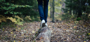person walking on log balancing