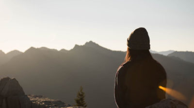 woman sitting on top of mountain in meditation