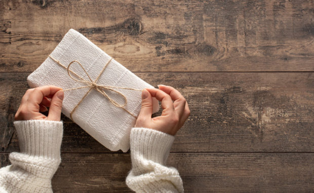 woman's hands tying string on gift with white wrapping paper