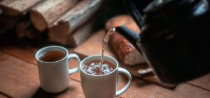 kettle pouring tea into mug in front of firewood