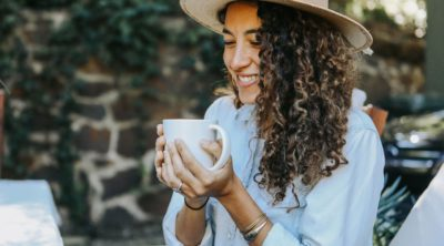 woman drinking cup of tea with Best Herbs for Anti-Aging Skin